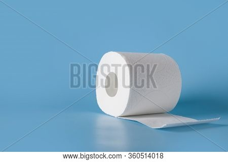 Roll Of Soft Toilet Paper On Blue Table With Space For Text. Increased Potential. High Unexpected De