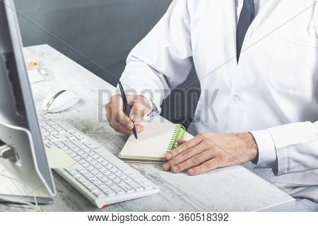 Young Male Hands In White Clothers Writes Something In White Notebook