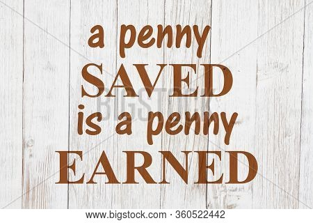 Old Money Saying A Penny Saved Is A Penny Earned On Weathered Whitewash Wood