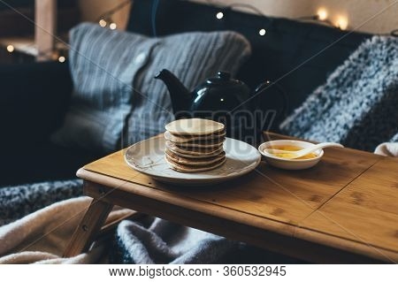 Fresh Homemade Banana Pancakes With Honey Or Syrop And Pot With Hot Tea On Wooden Tray In Cozy Room.
