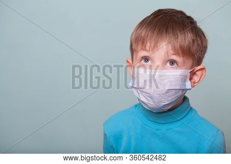Baby Boy In Medical Mask Isolate On A Blue Background. Concept Of Coronavirus, Quarantine, Epidemic,