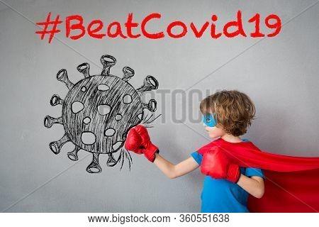 Superhero Child Beat Covid-19. Super Hero Kid Punching On The Drawn Coronavirus. Winner And Success