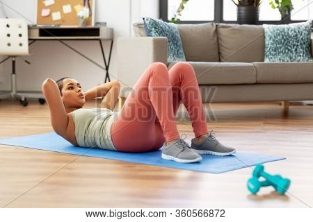 sport, fitness and healthy lifestyle concept - african american woman making abdominal exercises or crunches at home