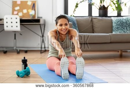 sport, fitness and healthy lifestyle concept - happy smiling african american woman with wireless earphones stretching at home