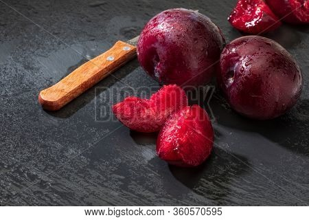 Appetizing And Healthy Red Plums, Whole And Cut Into Segments With A Rustic Appearance On A Black Ba