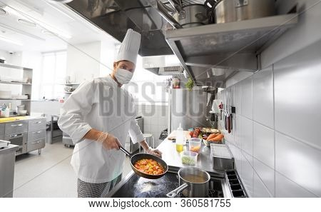 health, safety and pandemic concept - male chef cook wearing face protective medical mask for protection from virus disease cooking food in frying pan at restaurant kitchen