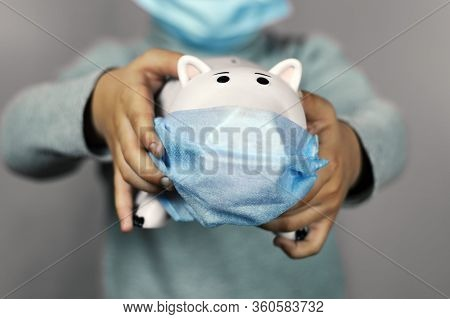 A Little Boy Holding A Piggy Bank In Face Mask. Symbol Of Poor Home Budget. Personal Budgeting Durin