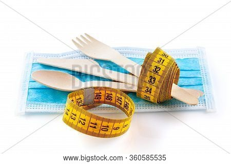Wooden, Disposable Tableware And Measuring Tape On A Medical Mask. Diet Or Quarantine Healthy Eating