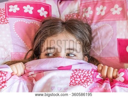 Scared And Anxious Girl In Bed Looking To See What Happens