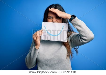 Young beautiful brunette positive woman holding card with smile emotion on mouth stressed with hand on head, shocked with shame and surprise face, angry and frustrated. Fear and upset for mistake.