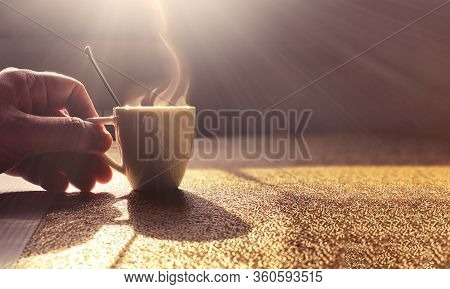 A Steaming White Ceramic Cup Containing Coffee On A Table Lit By The Light Of The Dawn Sun. A Male H