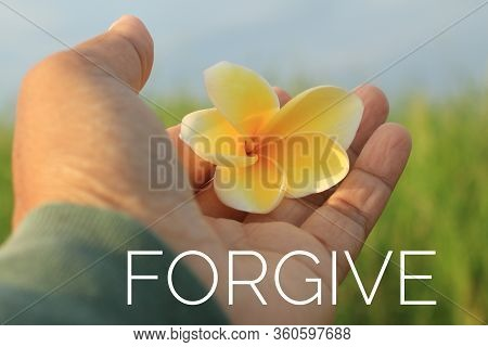 Inspirational Single Word - Forgive. With Woman Holding A  Yellow Bali Frangipani Flower In Hand On