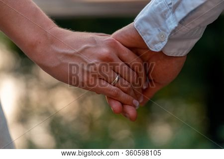 Close Up Of Bride And Groom Holding Hands With Wedding Rings On It. Giving Of Wedding Rings And Vows