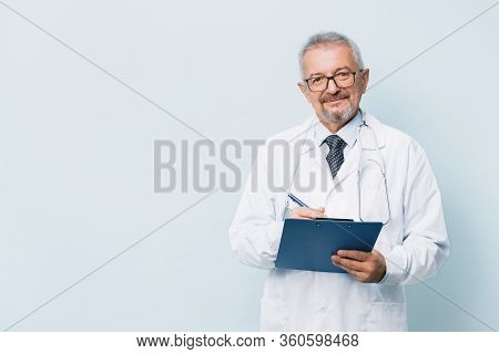 Elderly Bearded Male Doctor In White Uniform With A Stethoscope With A Blue Folder. Doctor On The Ba
