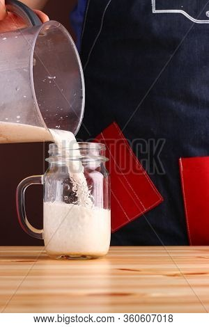 Milkshake Making On Wooden Table Closeup. Process Of Topping And Decorating Milkshake. Desset With C