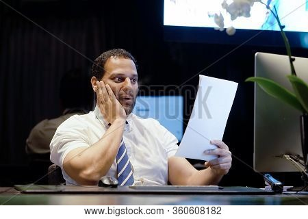 A Man-reception Hotel Worker Reading Negative News In Letter. Shocked Beauty Male Business Manager R