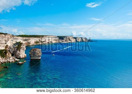 a view of the picturesque landscape of cliffs over the Mediterranean sea in Bonifacio, Corse, in France, highlighting the famous Grain de Sable sea stack in the foreground
