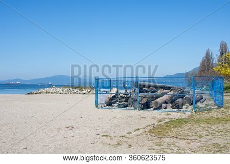 Logs Removed And Fenced Off At A Beach To Discourage People From Sitting Close To One Another During
