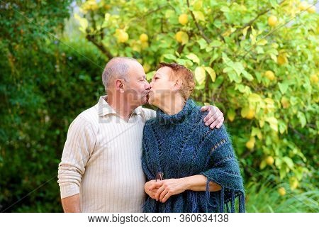 Portrait Of Happy Senior Couple Kissing In Outdoor Garden. Elderly Man And Woman Relaxing By The Par