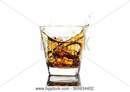 Whiskey Glass With Ice Splashes. Glass Of Splashing Whiskey With Ice Isolated On White