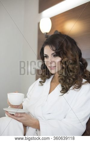 Beautiful Young Caucasian Sexy Girl In White Bathrobe Relaxing At Home With Cup Of Coffee On Leisure