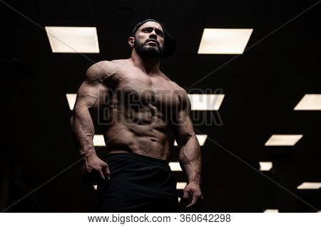 Muscular Aggressive Young Male With Beard In Dark Sport Gym