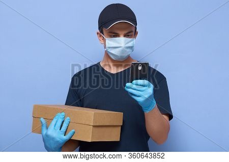 Horizontal Shot Of Delivery Man With His Smart Phone In Hands, Finding Write Delivery Address Or Cal
