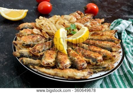 Fried Capelin, Sprats. Small Fried Fish On A Plate On A Black Background.