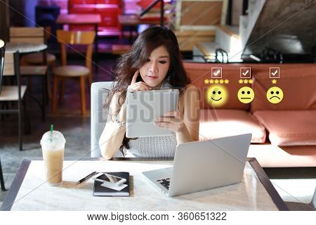 Beautiful And Young Asian Woman In Casual Dress Sitting And Using Tablet And Computer With Smiling F