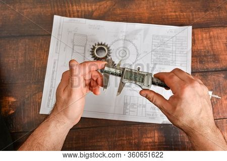 A Working Engineer Checks The Size Of A Bevel Gear With An Electronic Vernier Caliper Against The Ba