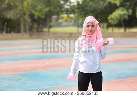 Athletic Young Asian Muslim Woman In Sportswear Standing And Lifting Dumbbells Public Outdoor For Mo