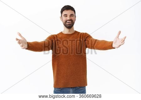 Portrait Of Happy And Friendly Bearded Man Give Warm Welcome To Dear Guest, Spread Hands Sideways In