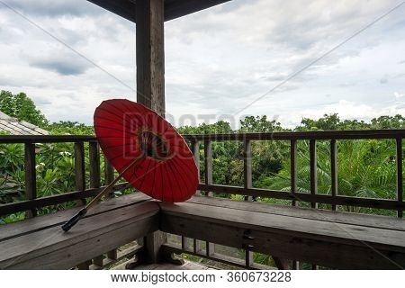 Red Paper Umbrella In Traditional Lanna House, Chiang Mai, Thailand
