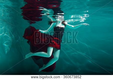 Beautiful Girl In A Red Dress Swims Under Water. Amazing Underwater Beauty Photo. Dive Under The Wat