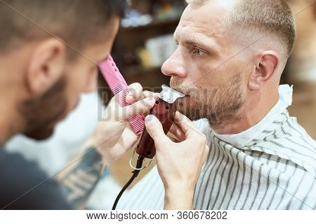 Close-up Side View Of A Cool Man At The Barber Shop Having His Mustache Cut With A Red Trimmer, Blur