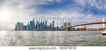 Wide Stiched Panorama Of Manhattan Downtown At Sunset From The Brooklyn Bridge Park.