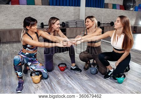 Group Of Four Young Motivated Sporty Girls Standing Together Forming Hand Stack Before Workout In Fi