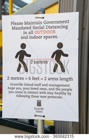 A Sign Posted At Granville Island Asking Patrons To Practice Social Distancing During The Covid-19 P