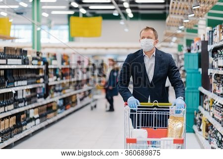 Photo Of Adult Man Wears Disposable Face Mask, Makes Shopping, Thinks About Protection And Prevent M
