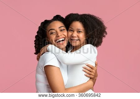 I Love My Mommy. Cheerful Little Black Girl Embracing Her Happy Mother While Posing Against Pink Bac