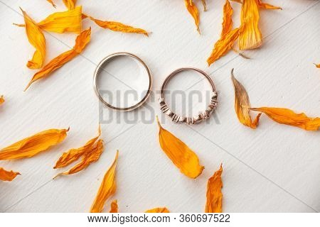 Two Wedding Rings For Bride And Groom Top Down View With Orange Dried Flower Petals