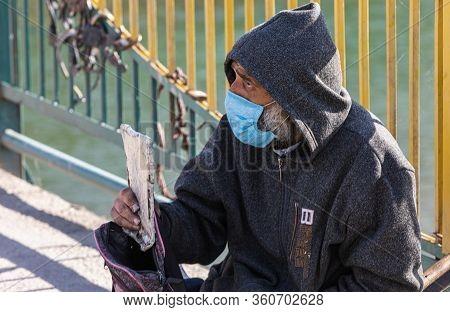 Uzhgorod, Ukraine - Apr. 10, 2020: Beggar Cripple In Protective Medical Mask Asks For Alms Holding A