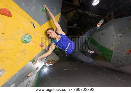 Rock Climber Woman Hanging On A Bouldering Climbing Wall, Inside On Colored Hooks