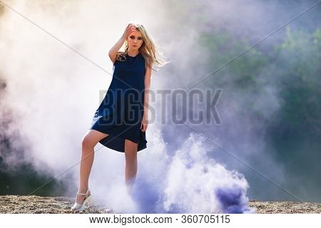 Young Beautiful Blond Woman In Blue Mini Dress And Floral Wreath Standing And Trying Water On Summer