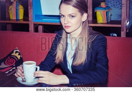 Contemplative Young Woman Drinking Coffee Clutching A Mug On Her Hands As She Stares Ahead At You Ca