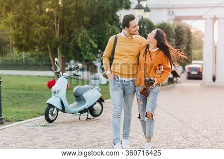 Enthusiastic Girl In Bright Orange Sweater Exploring Town With Her Boyfriend Which Carrying Backpack
