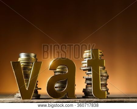 gold alphabet vat -value added tax against stack of coins