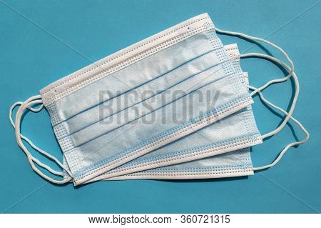 Surgical Disposable Face Masks On Blue Background. Top View. Medical Blue Masks. Medical Respiratory