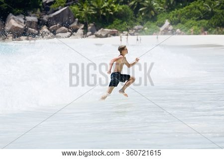 Young Boy Enjoys The Summer Holiday At Beach, Escaping From Big Splashing Wave.
