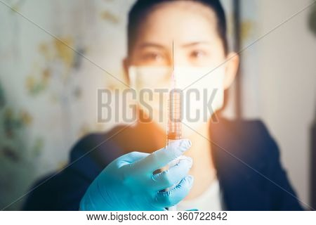 Cute Female Doctor In A Medical Protective Mask Holds A Syringe With A Vaccine In Her Hands. Against